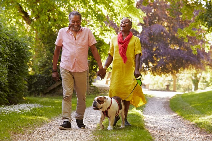 photo of mature couple walking dog
