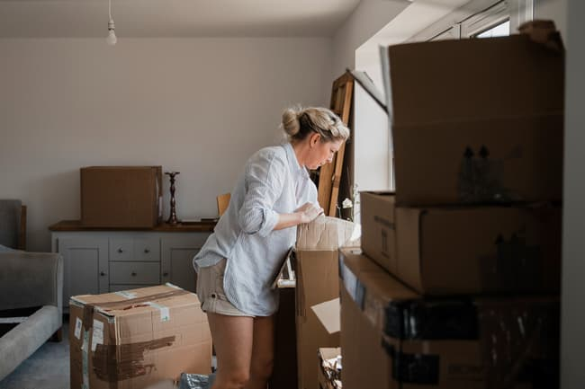 photo of woman unpacking boxes
