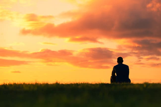 photo of man watching sunset