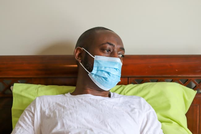photo of man sick in bed