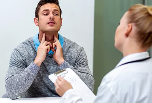 man explaining neck pain to doctor