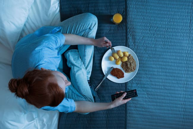 photo of woman eating on bed at night
