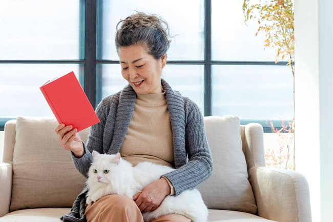photo of woman relaxing with cat