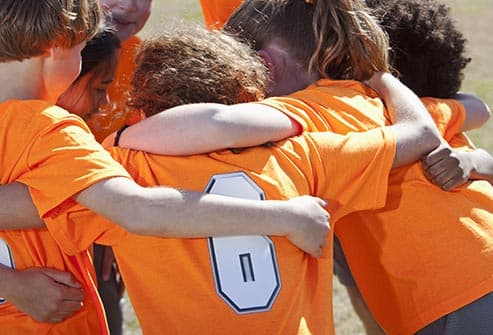 childrens sports team in huddle