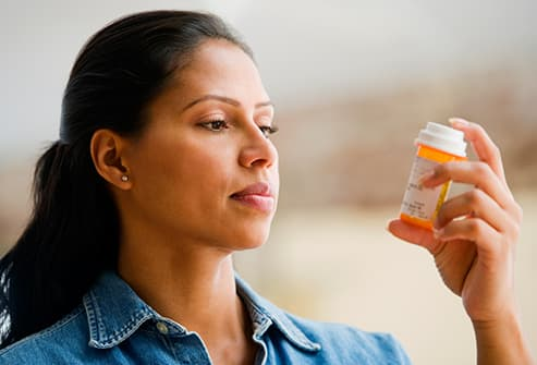 woman looking at medicine bottle
