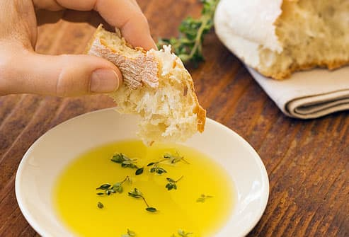 Man dipping bread in olive oil