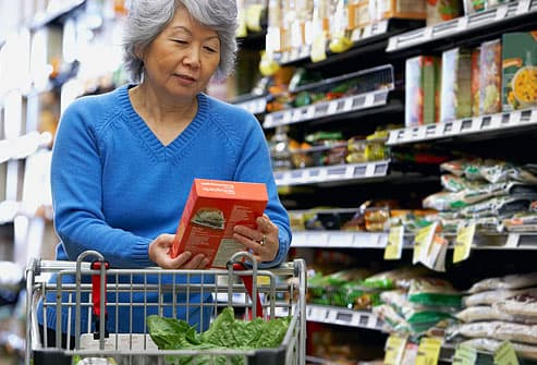 Senior Asian woman reading label at grocery store