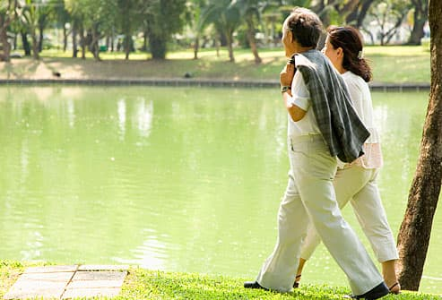 man and woman walking beside pond