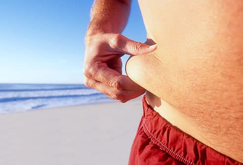 Man pinching fat on waist , beach in background