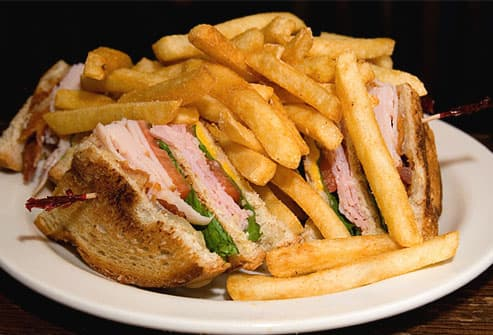 Club sandwich and fries on white plate