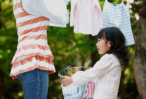 girl helping with laundry