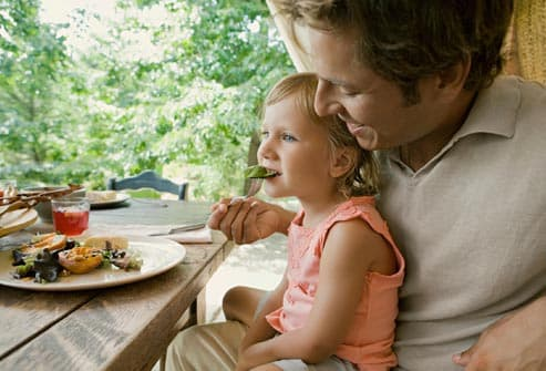 Dad feeding daughter at table