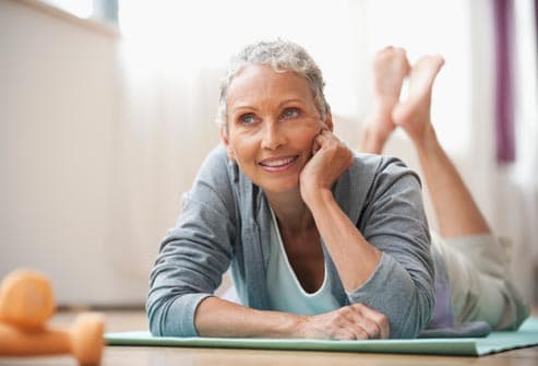 Woman on yoga mat smiling