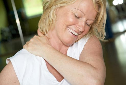 smiling woman rubbing shoulder