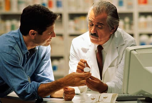 Mature pharmacist explains medication to customer