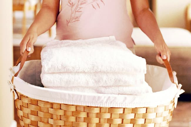 photo of woman carrying basket of clean towels