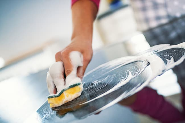 photo of man cleaning countertop
