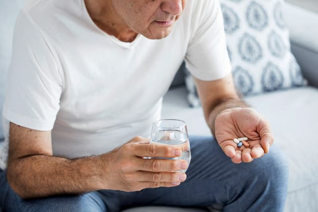 photo of man taking medication