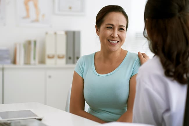 photo of woman talking to doctor
