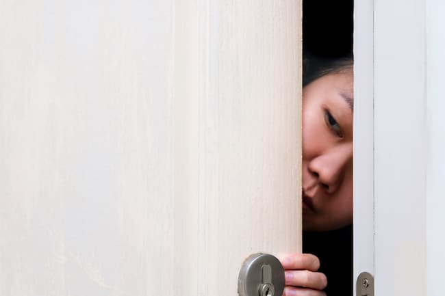 photo of woman peering out from door