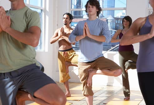 adults practicing yoga, standing on one leg