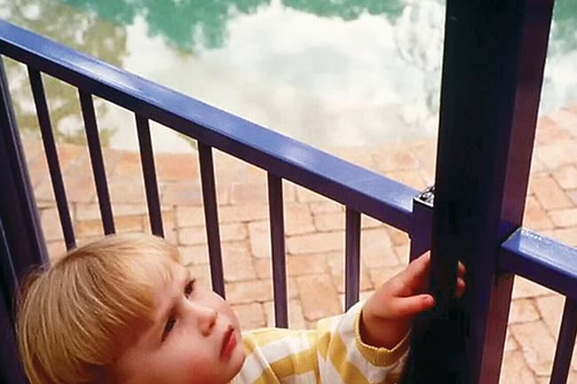 child by swimming pool fence
