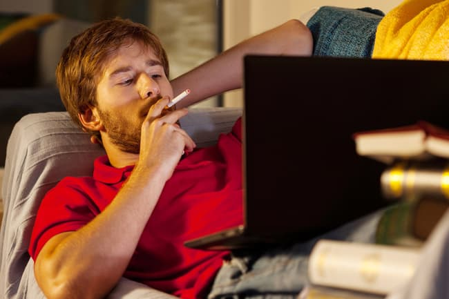 man smoking on sofa