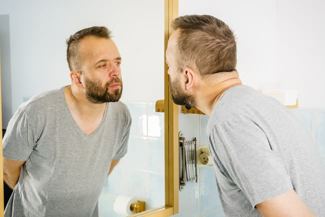 photo of man looking at himself in the mirror
