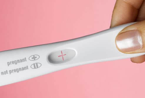 Woman's hand holding pregnancy test