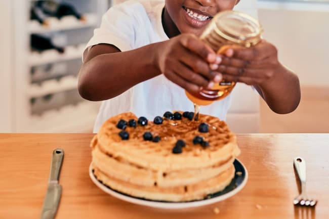 photo of young boy pouring honey on waffles