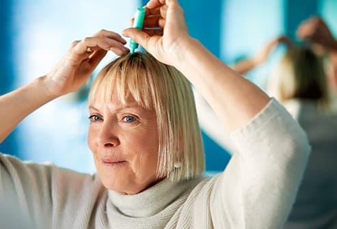 woman applying scalp treatment