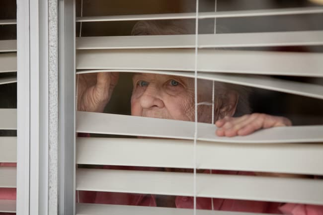 photo of senior woman looking out of blinds