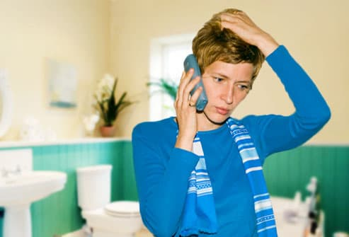 Concerned woman on phone in bathroom