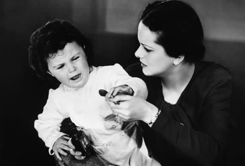 Vintage photo of mother giving child medicine