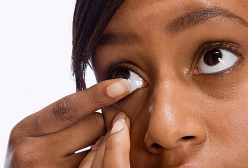 woman removing contact lens