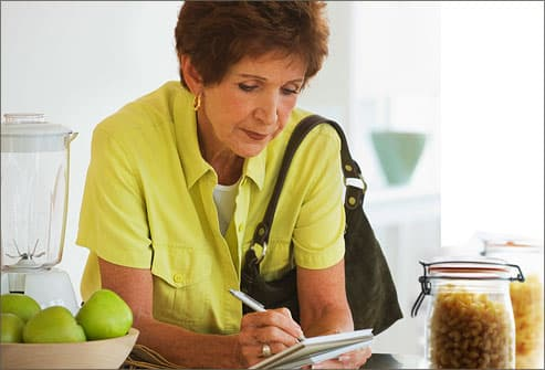 Woman making list before going grocery shopping