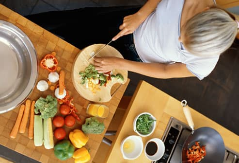 Overhead view of woman chopping many vegetables