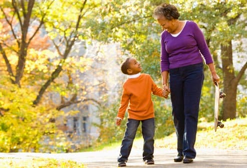 grandmother and grandson walking in park
