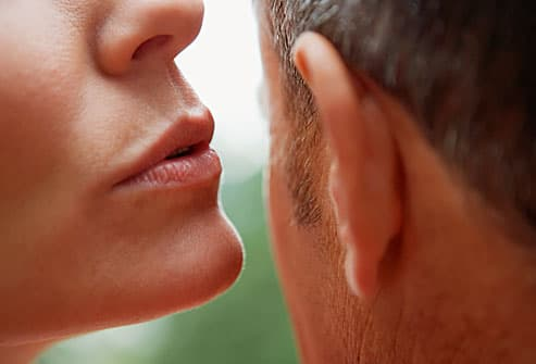 Woman whispering in mans ear