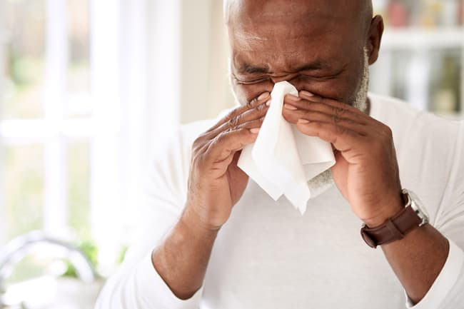photo of man blowing nose