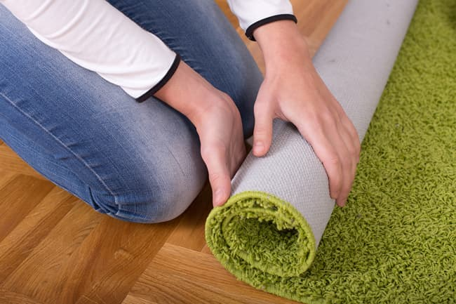 photo of person rolling up carpet