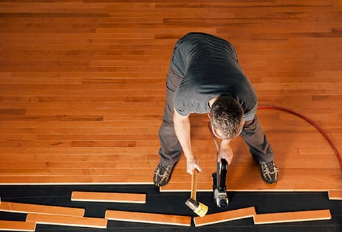 man laying hardwood flooring