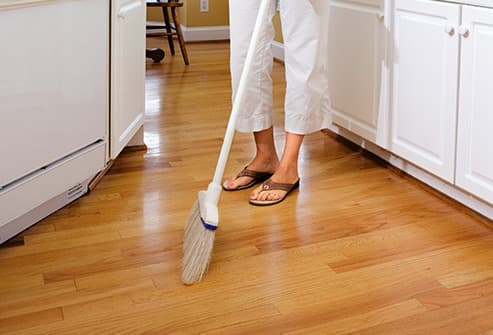 woman sweeping kitchen floor