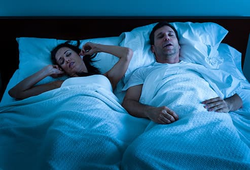 man snoring next to wife