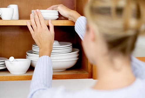 woman putting up dishes