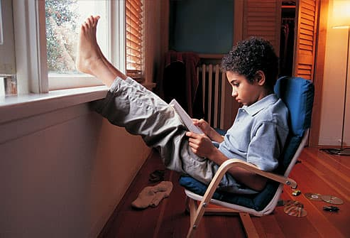Preteen boy reading with feet on window