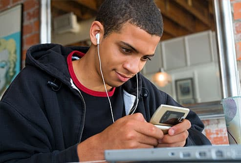 Teen boy texting and listening to music