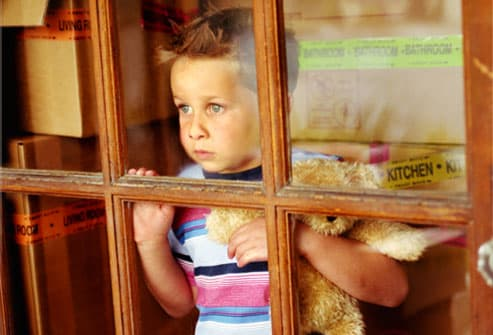 Stressed young boy looking through window