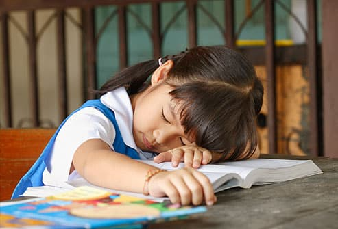 Young girl sleeping on school books