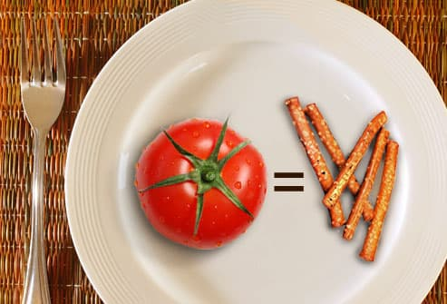 Plate with tomato and equally five dense pretzels